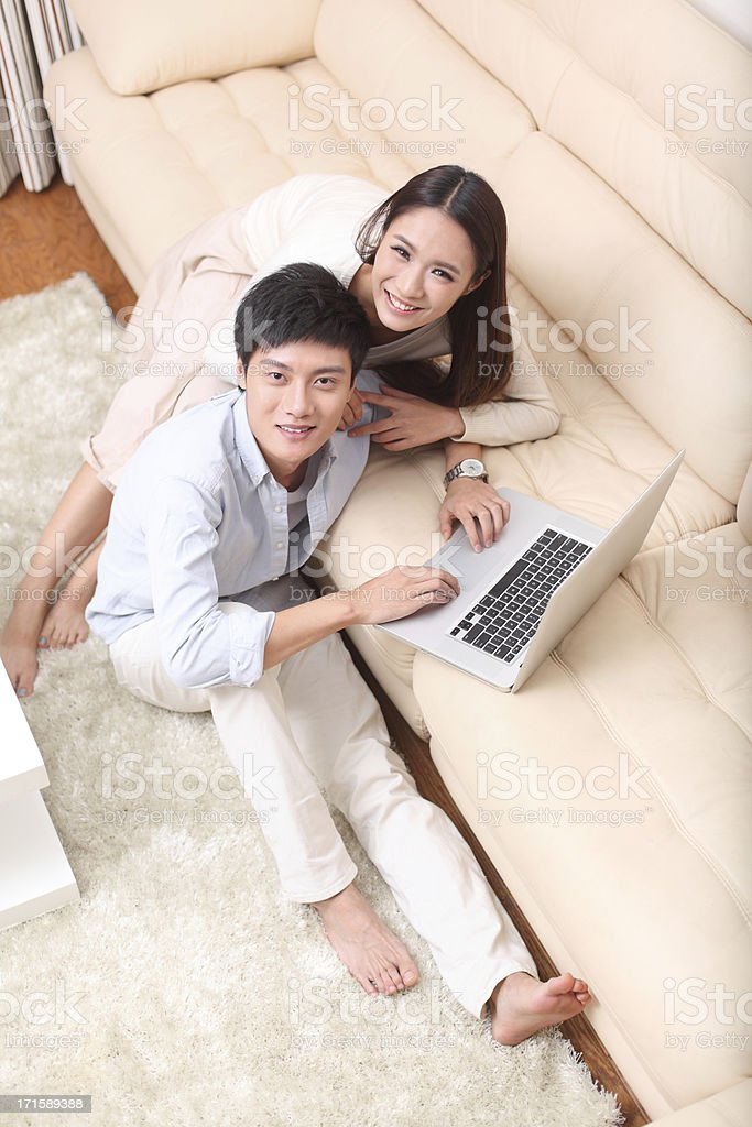 Couple sitting on couch and using laptop royalty-free stock photo