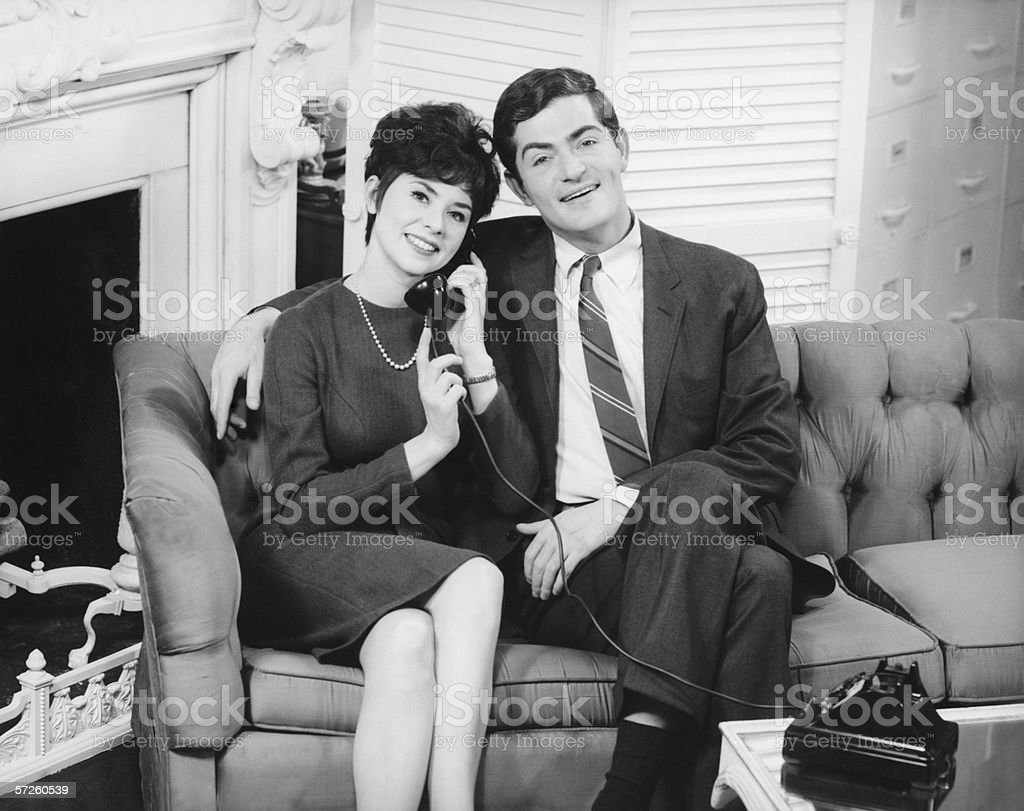 Couple sitting on couch in living room, woman on phone, (B&W), portrait stock photo
