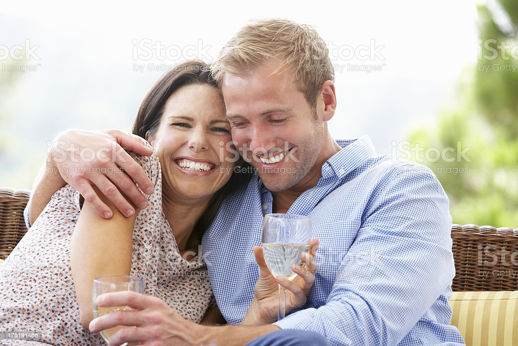 Couple Sitting On Outdoor Seat Together stock photo