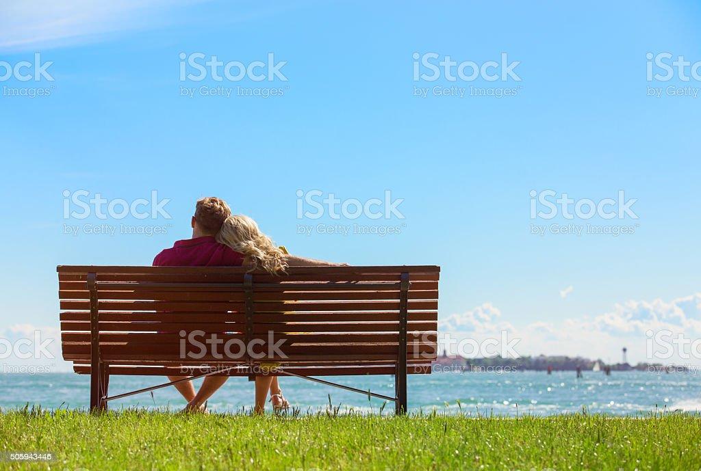 Couple sitting on park bench stock photo