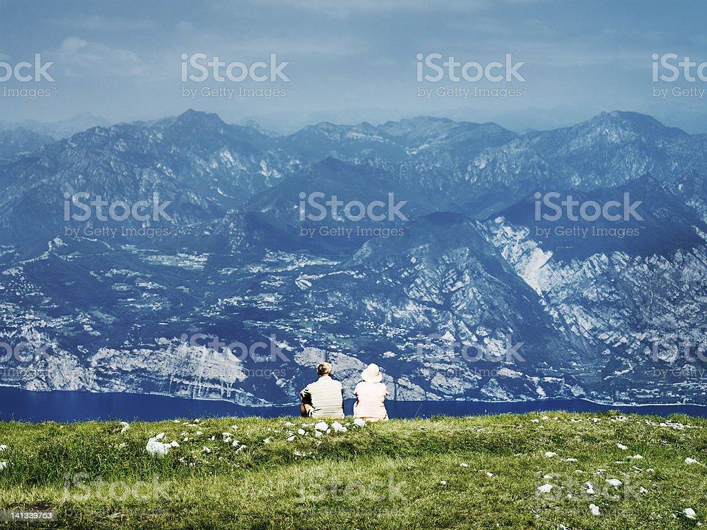 Couple sitting on rural hillside stock photo