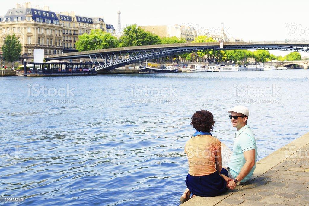 Couple sitting on Seine River banks stock photo