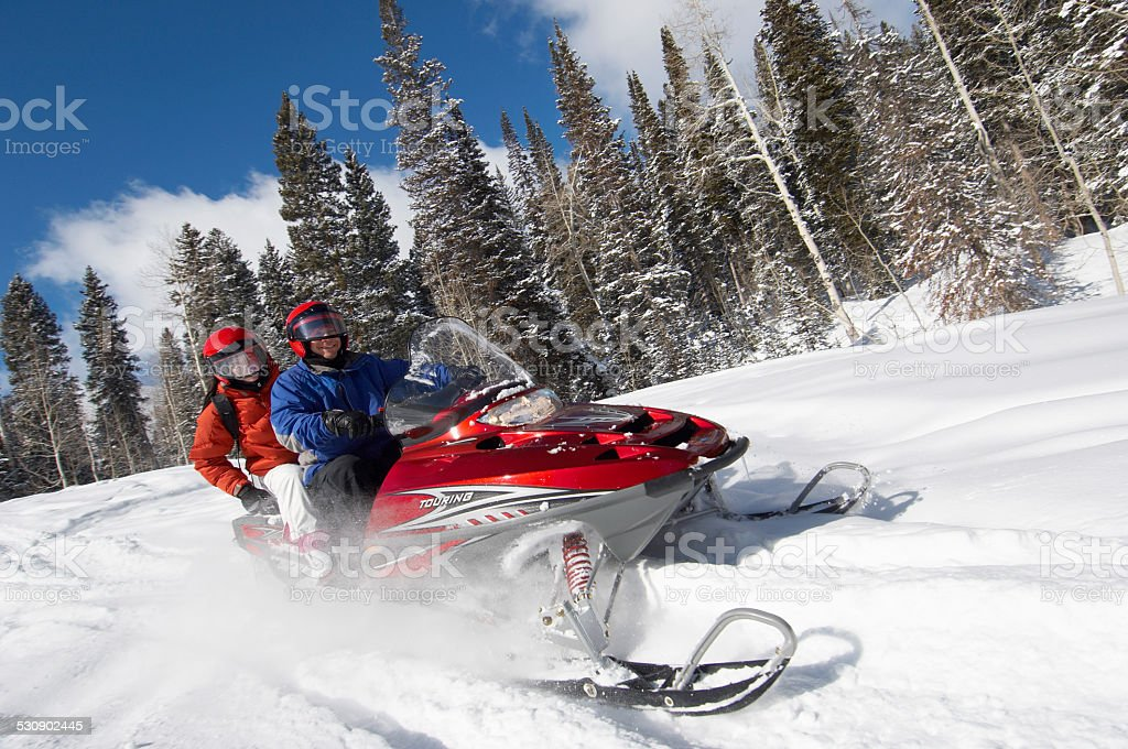 Couple Sitting on Snowmobile stock photo
