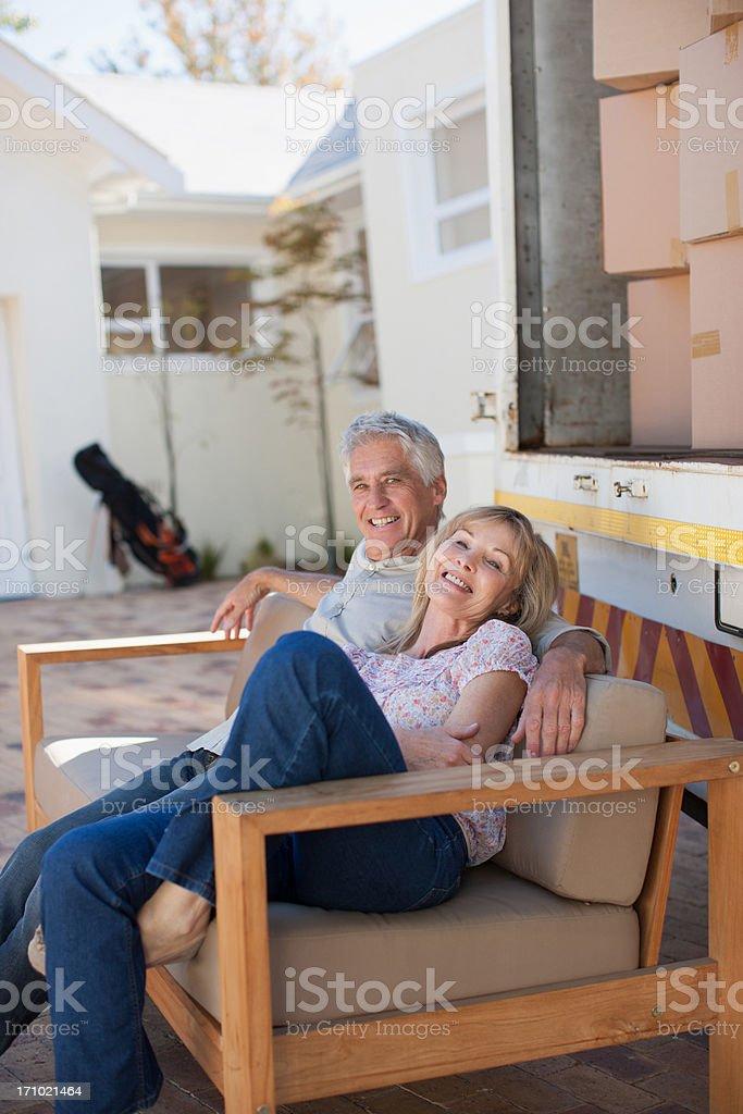 Couple sitting on sofa beside moving van royalty-free stock photo