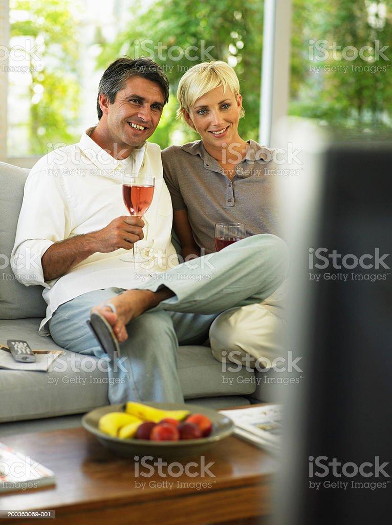 Couple sitting on sofa, holding wine glasses, smiling royalty-free stock photo