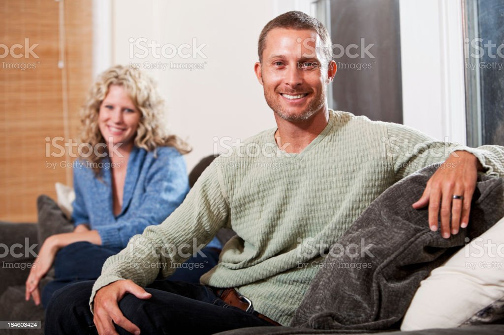 Couple sitting on sofa, man in focus stock photo