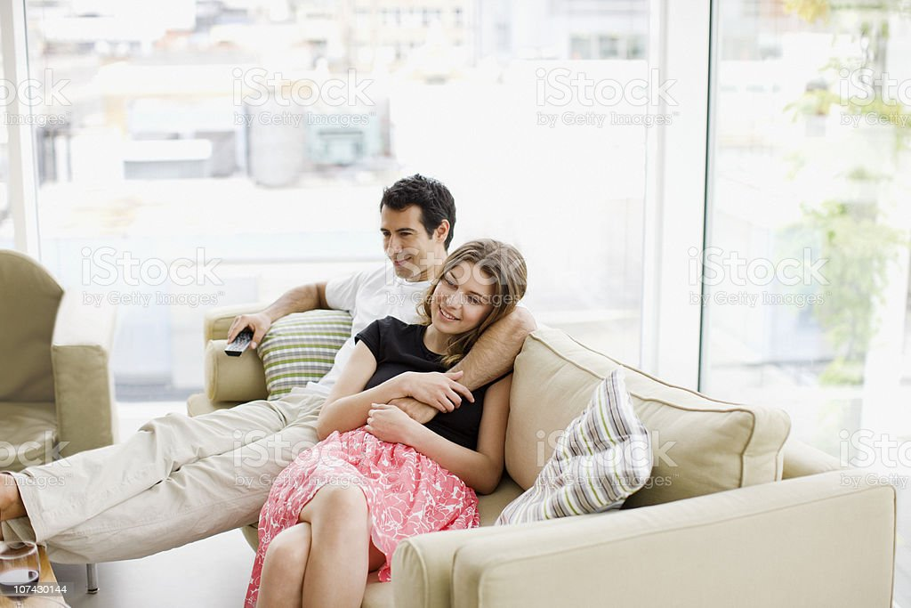 Couple sitting on sofa watching television stock photo