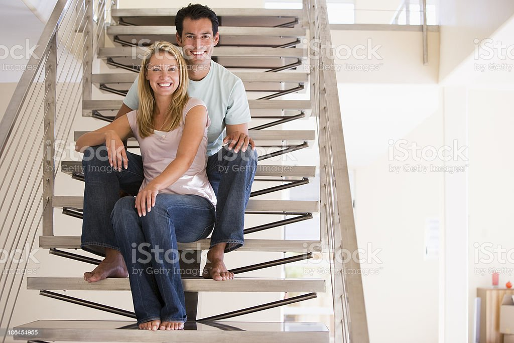 Couple sitting on staircase smiling stock photo