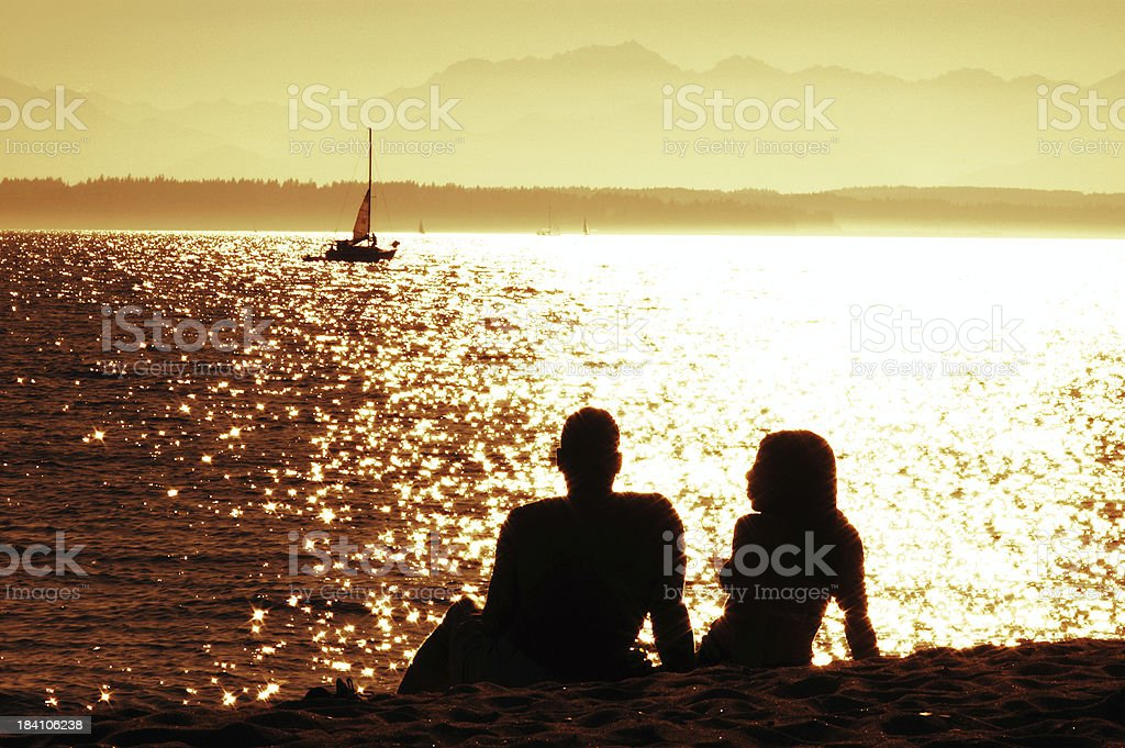 Couple Sitting on the Beach - Silhouette royalty-free stock photo