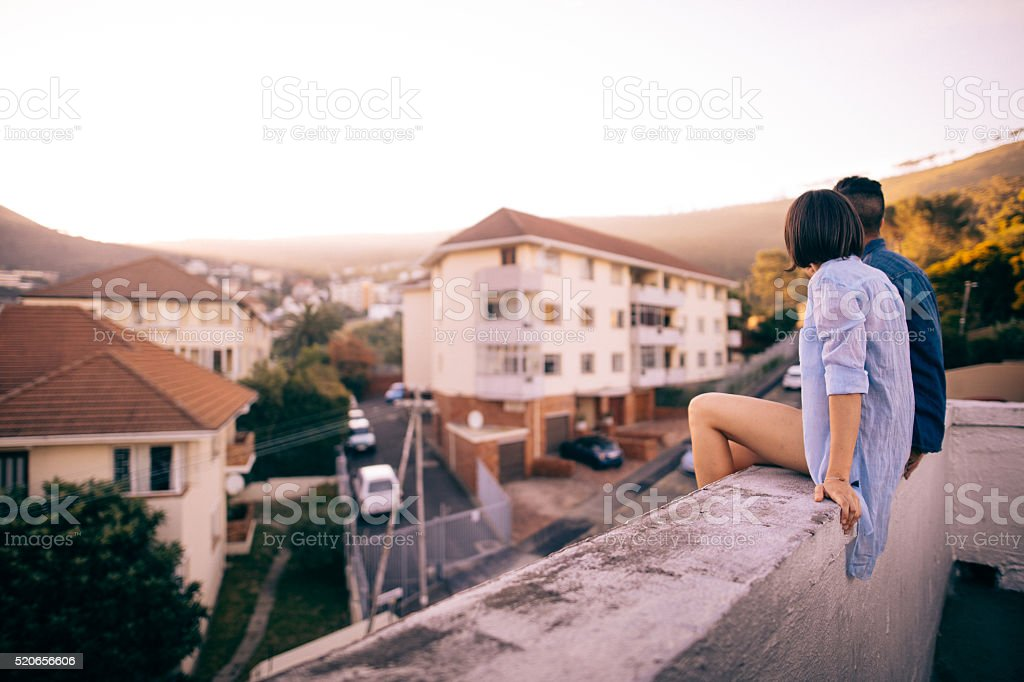 Couple sitting on the rooftop enjoys sunset over the city stock photo