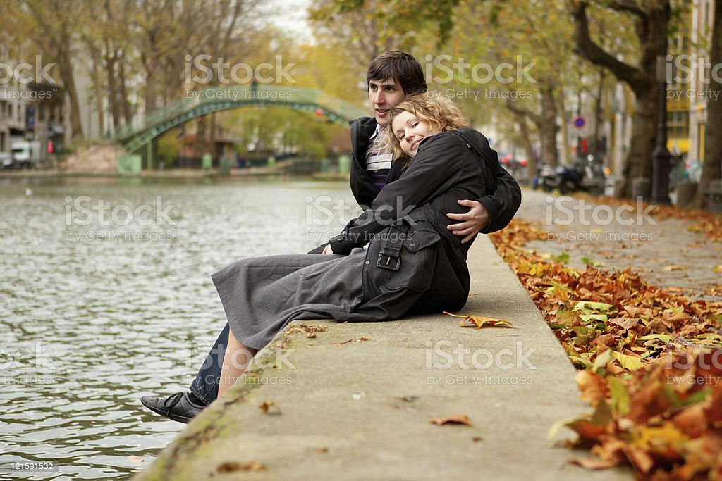 Couple sitting on the side of a canal in Saint-Martin Paris stock photo