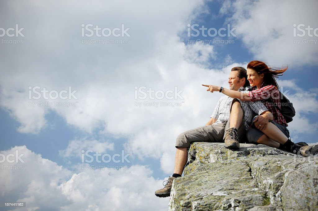A couple sitting on top of a mountain stock photo