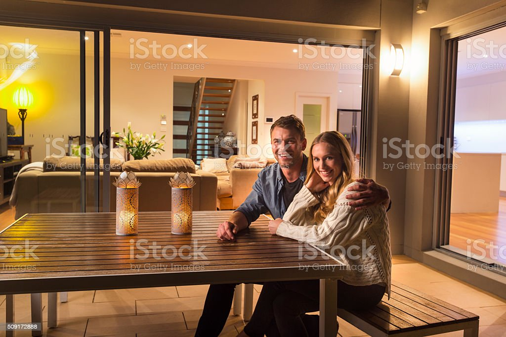 Couple sitting outside their home at night. stock photo