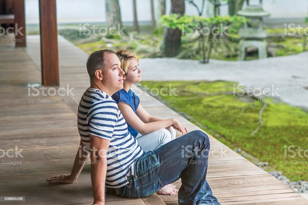 Couple sitting relaxing in Japanese gardens stock photo