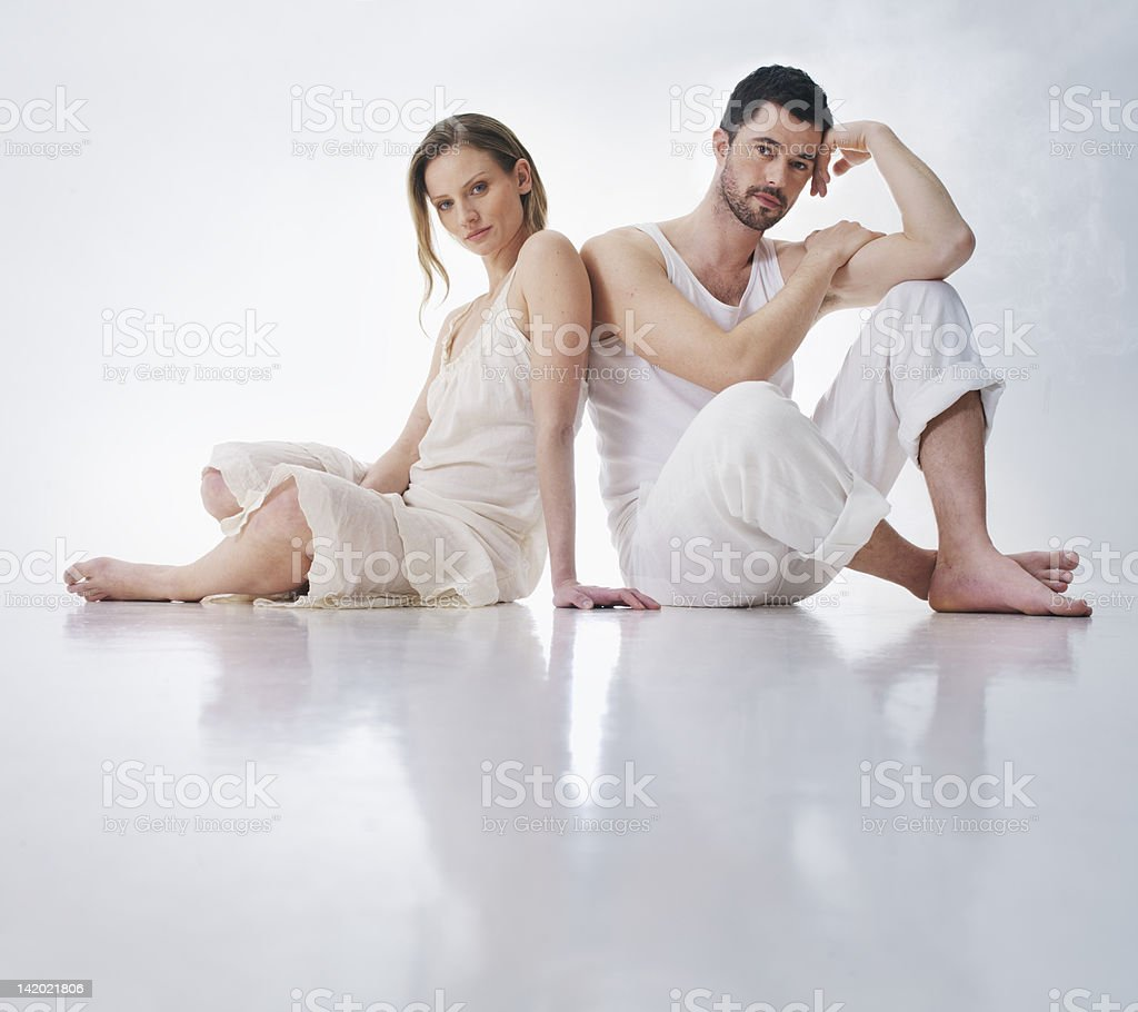 Couple sitting together on floor stock photo
