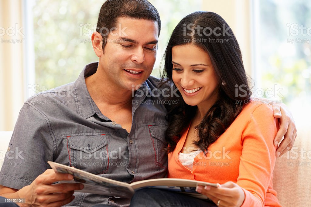 A couple sitting together reading a magazine royalty-free stock photo