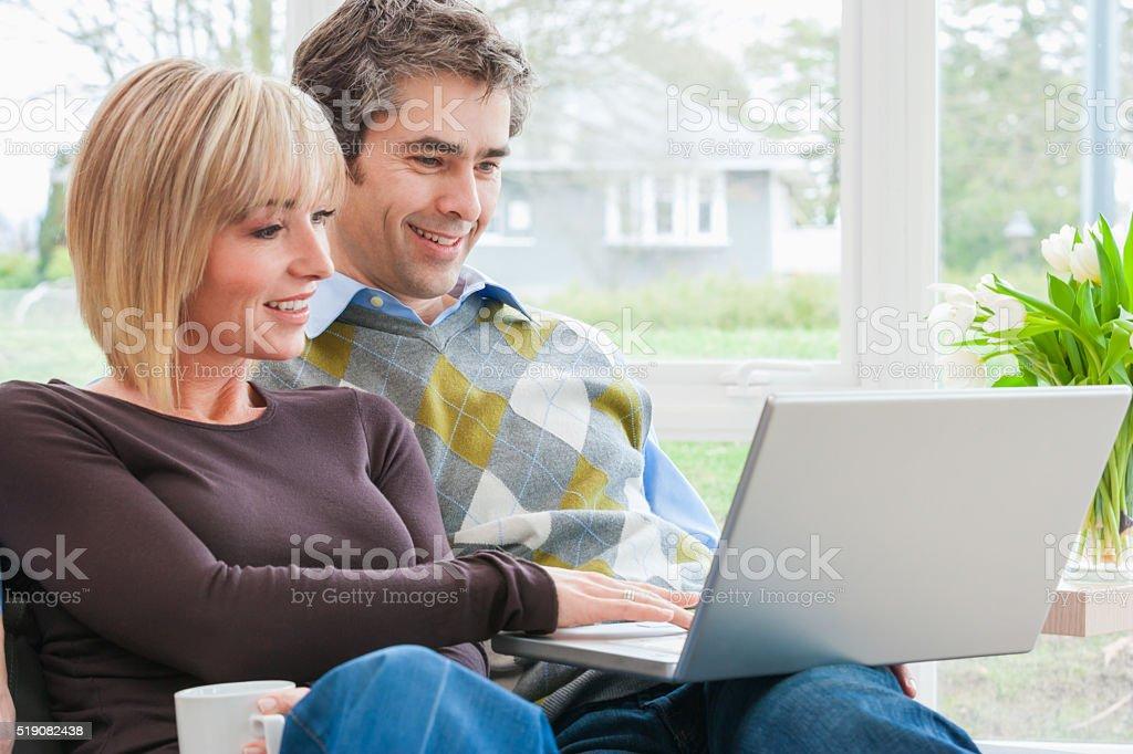 Couple sitting together using laptop stock photo