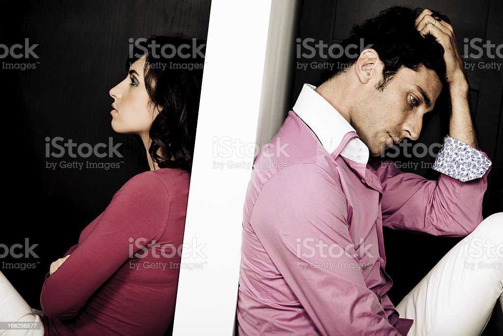 Couple sitting with backs to each other royalty-free stock photo