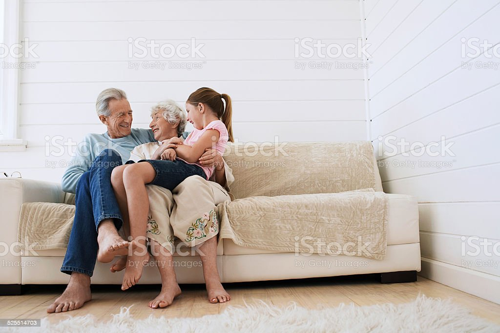 Couple Sitting With Granddaughter On Couch stock photo