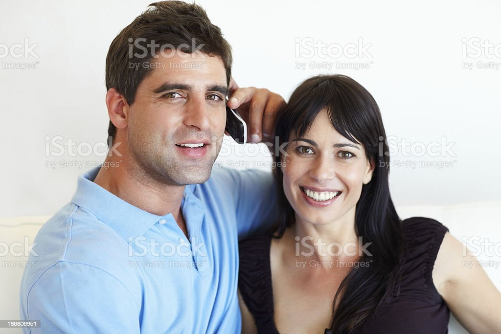 Couple sitting with man talking on cellphone royalty-free stock photo