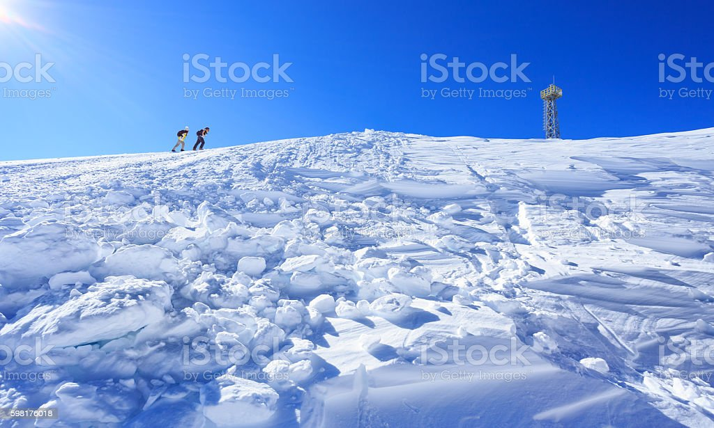 Couple skiers climbing up to the top of the mountain stock photo