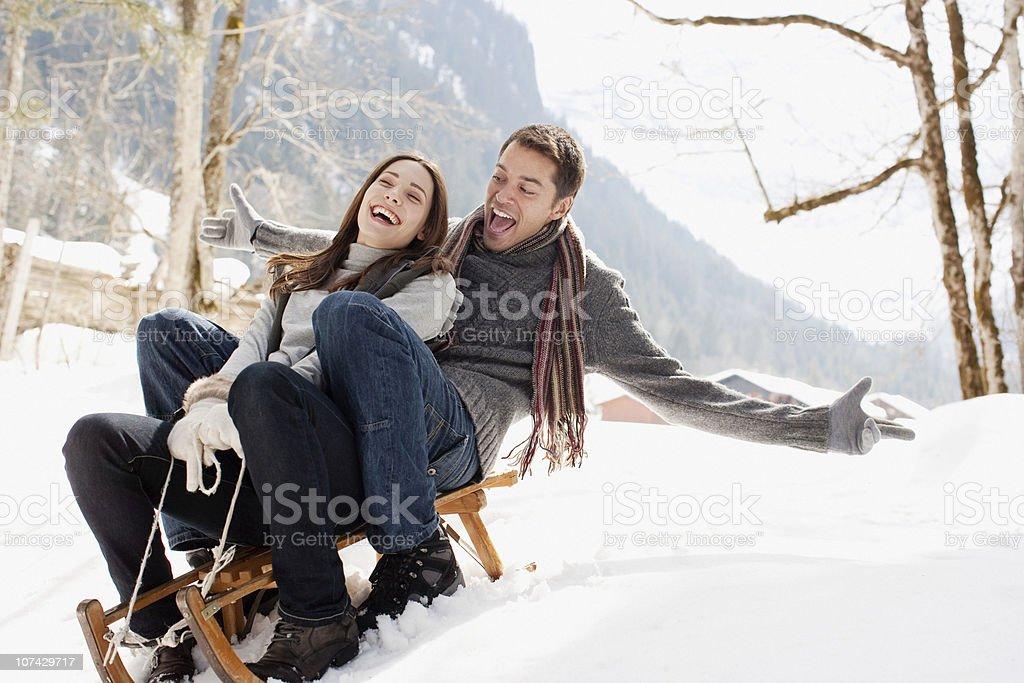 Couple sledding in snow royalty-free stock photo