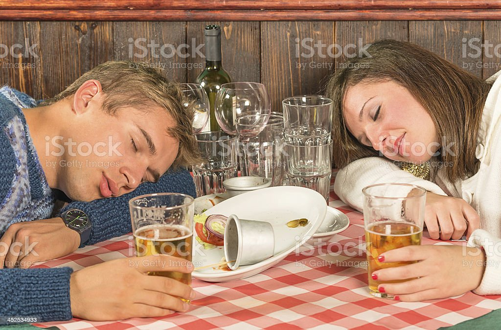 Couple sleeping after a huge alcoholic Dinner stock photo
