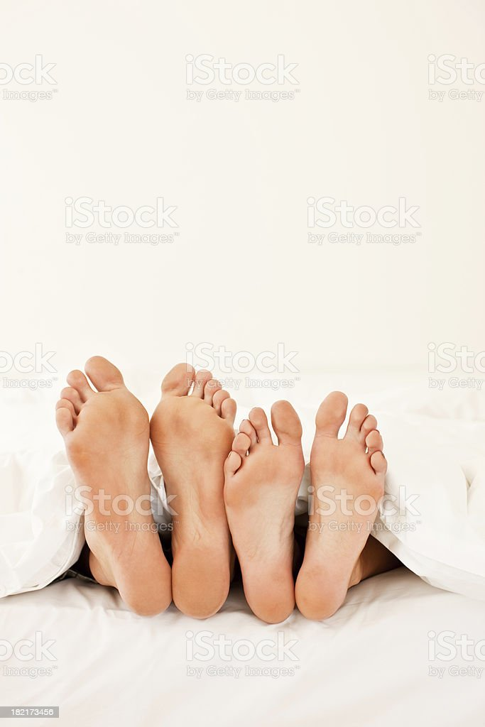 Couple sleeping in bed, focus on their feet royalty-free stock photo