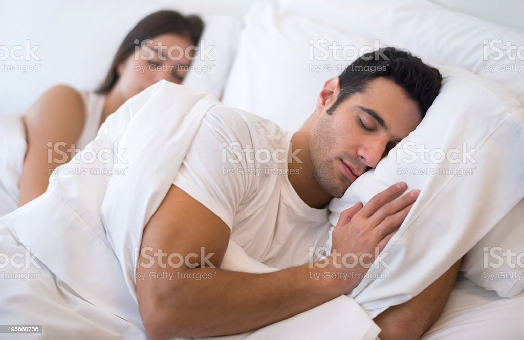 Couple sleeping in bed stock photo