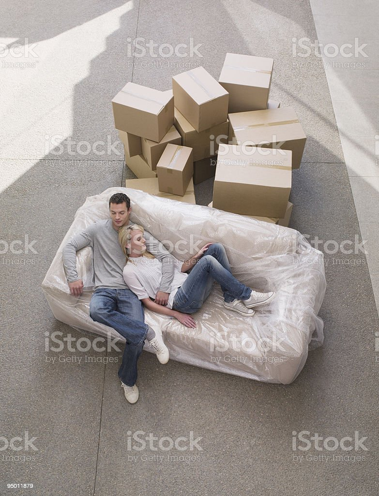 Couple sleeping on sofa wrapped in plastic royalty-free stock photo