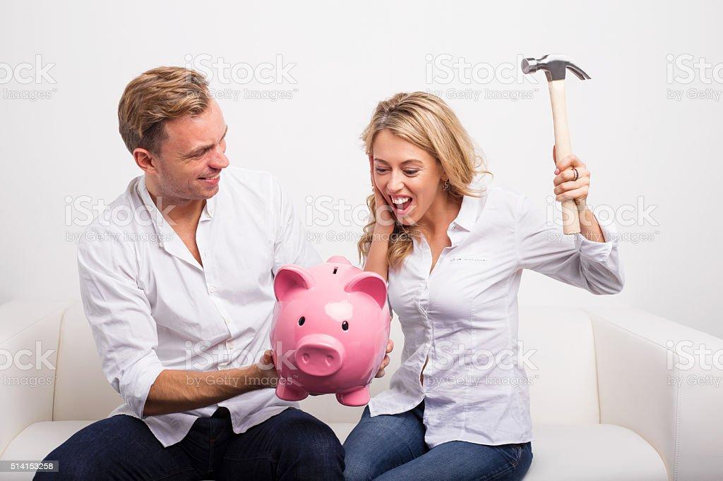 Couple smashing piggy bank with hammer stock photo