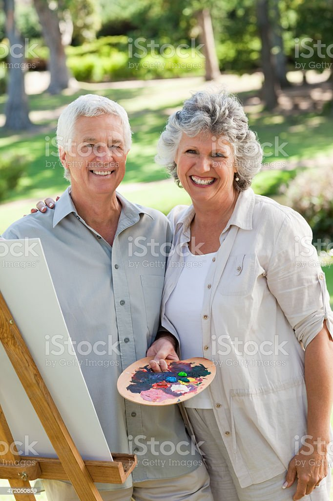 Couple smile at camera while painting royalty-free stock photo