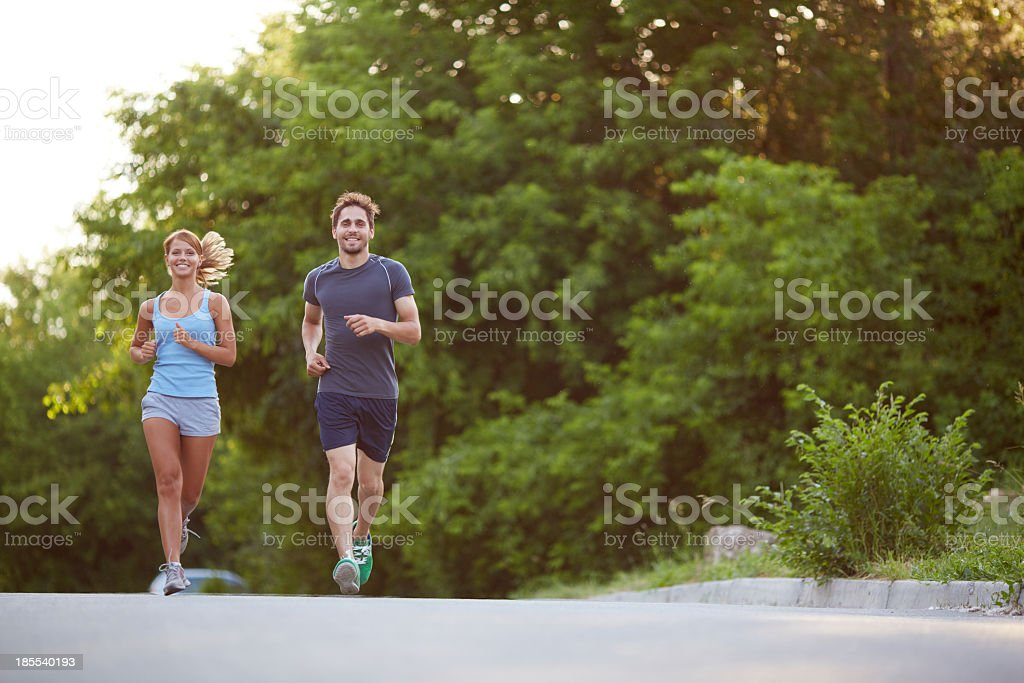 A couple smiles on their morning jog royalty-free stock photo