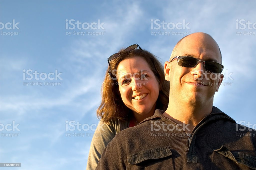 Couple smiling against blue sky with sun shining their faces royalty-free stock photo