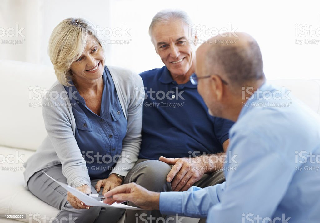 Couple smiling and listening to financial planner royalty-free stock photo