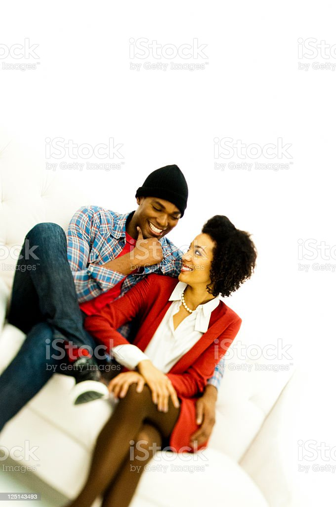 Couple smiling at each other on couch stock photo