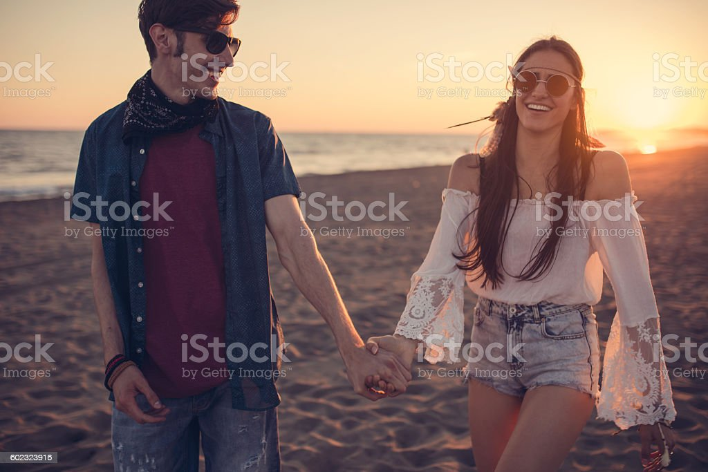 Couple smiling at each other on the beach stock photo