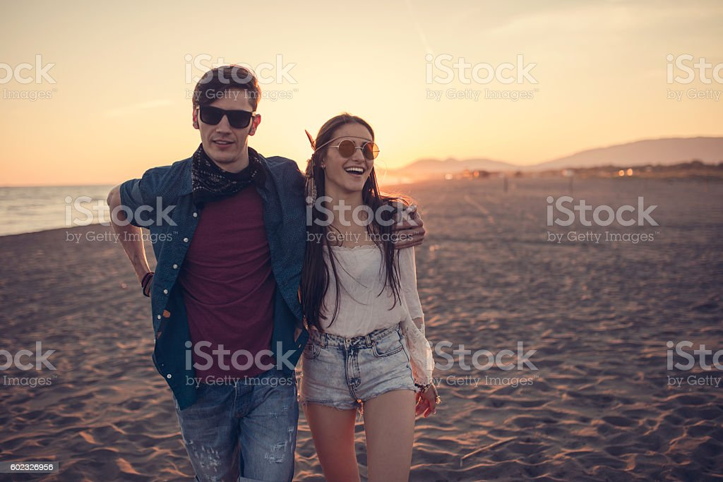 Couple smiling at the camera on the beach stock photo