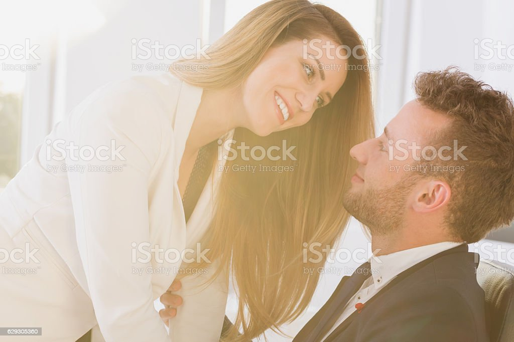 Couple smiling in the office stock photo