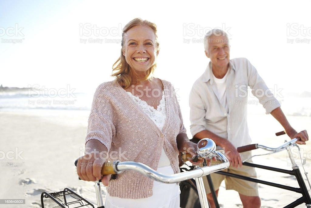 Couple smiling while taking bike ride on beach stock photo