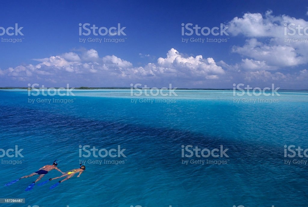 Couple snorkeling in beautiful blue water stock photo