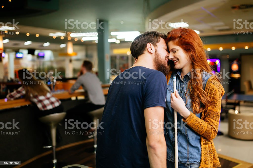 Couple spending time together by playing pool stock photo