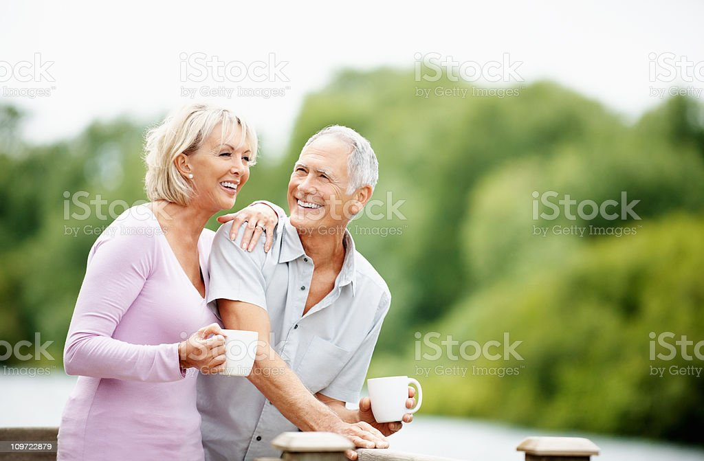Couple spending time together, holding cup of tea or coffee stock photo