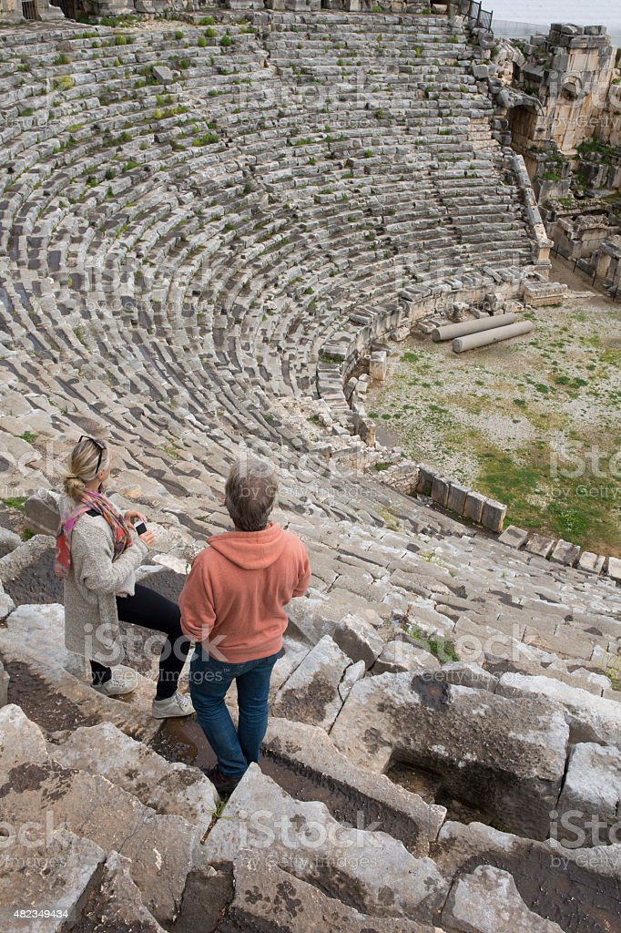 Couple stand on theatre steps of ancient Greek ruin stock photo
