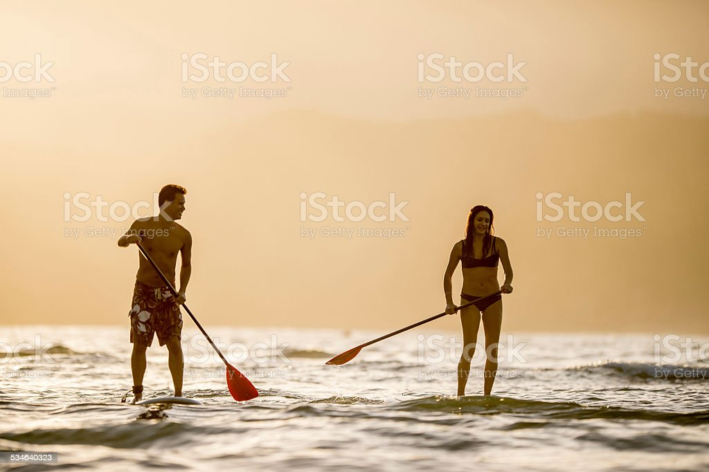 Couple stand up paddleboarding SUP stock photo