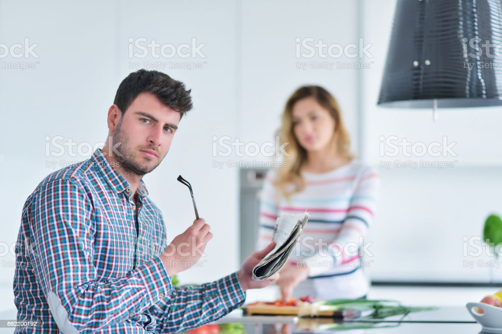Couple standing and sitting at the kitchen while smiling stock photo
