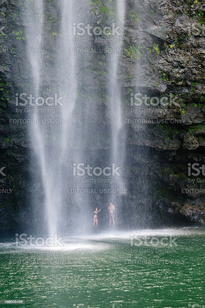 Couple standing behind Hanakapi'ai Falls on Kauai, Hawaii stock photo
