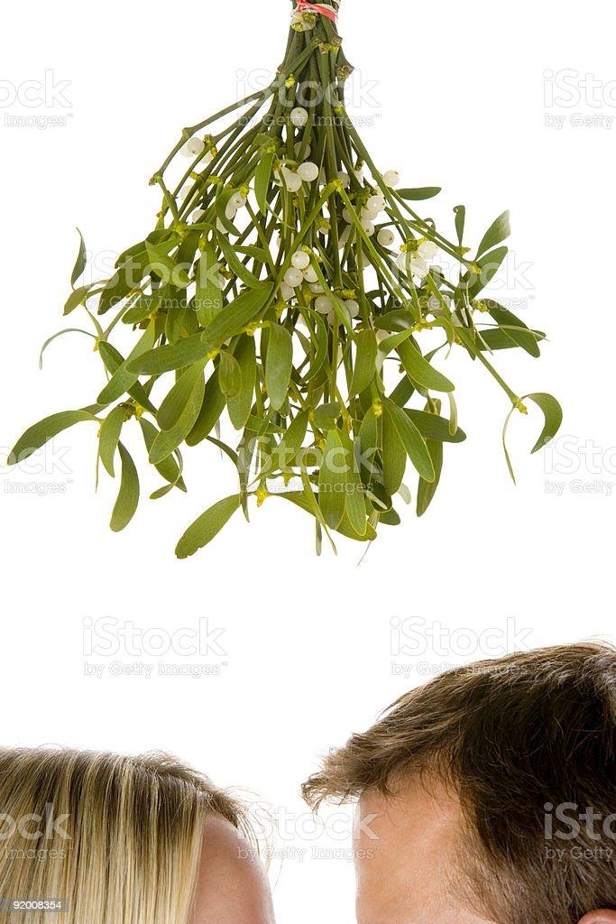 Couple standing beneath mistletoe stock photo