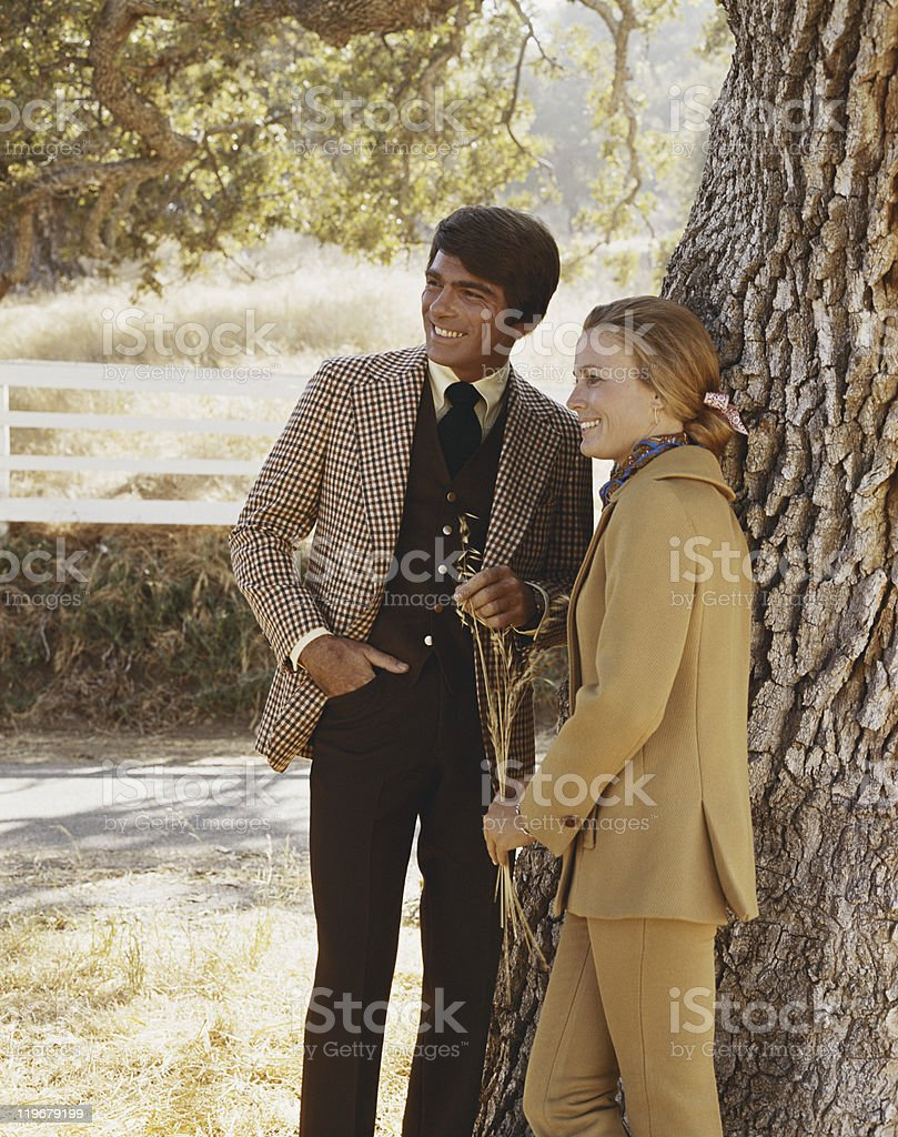 Couple standing beside tree trunk, smiling royalty-free stock photo