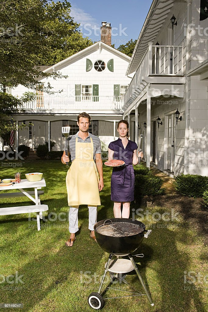 Couple standing by barbecue royalty-free stock photo